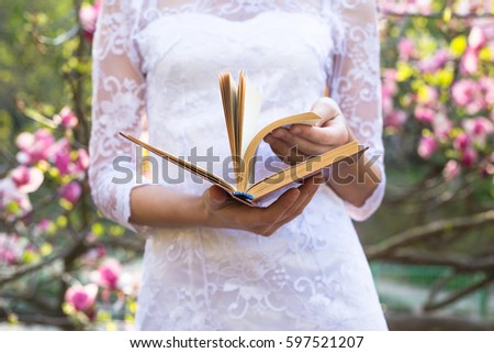 Young pretty girl with book relax in beautiful garden