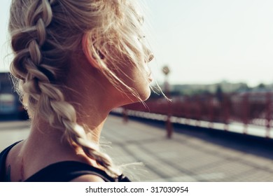 Young pretty girl with braided pigtails. Soft sunny color outdoors portrait.