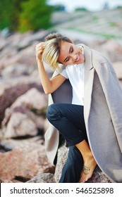 Young pretty girl with closed eyes in a draped over the shoulders of a coat sitting on a rock barefoot and smiling fun.