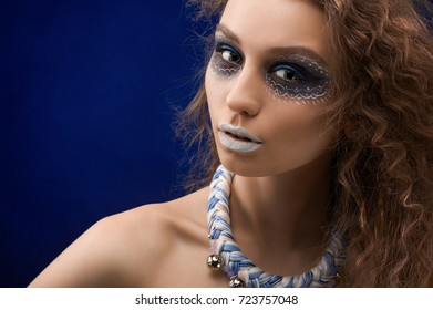 A young pretty girl with colorful ornament painted on her face. She has healthy skin tone and brown hair. Her make-up and hairdress are wonderful. The portrait was taken on the dark background.