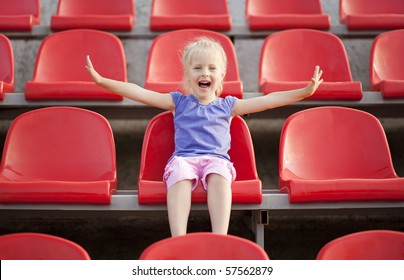 Young pretty girl cries and sitting on the audience bleachers