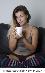 Young pretty girl with cup of coffee sitting in armchair at home wearing a shirt, panties and knee-socks