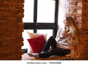 Young pretty girl with cup sitting and relaxing near window