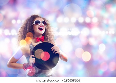 Young pretty girl dj at disco party holding vinyl