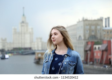 Young pretty girl dreamily smiles on Moscow city background outdoor, Russian student