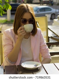 Young pretty girl drinks a cup of hot beverage, outdoor