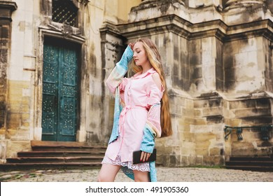 Young pretty girl with extra long blonde hair in light pink dress and knitted sweater on the city streets. Beautiful fashion woman outdoors.