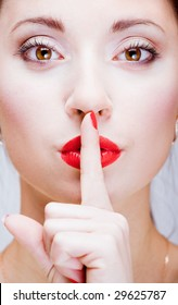 Young pretty girl with a finger by lips