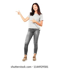 young pretty girl full body smiling and pointing to the side with both hands, towards the place where the publicist may show a concept.