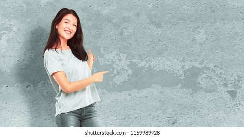 young pretty girl full body smiling and pointing upwards with both hands, towards the place where the publicist may show a concept.