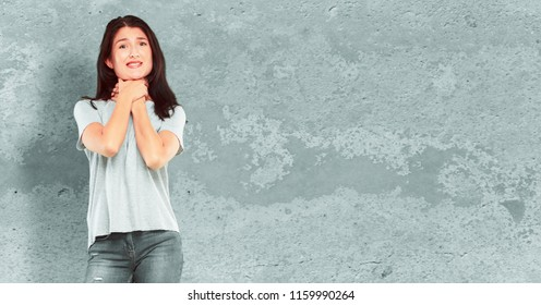 young pretty girl full body screaming, looking surprised, stressed and terrified, with a gesture of choking with both hands