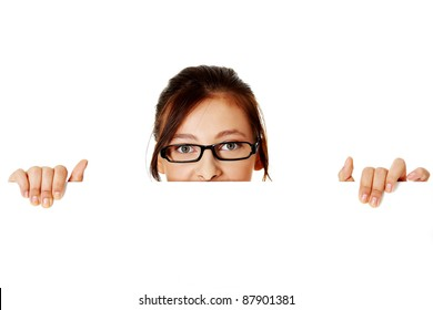 Young pretty girl in glasses hiding behind sheet of paper over white background.