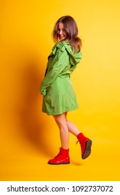 Young pretty girl with green oilskin with hood on yellow studio background