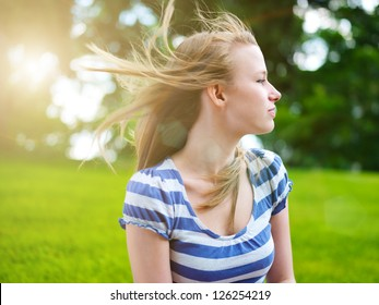 young pretty girl with hair blowing in the wind outside