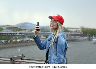 Young pretty girl happy smiles and makes self photo on smartphone on Moscow city and river background outdoor, Russian student