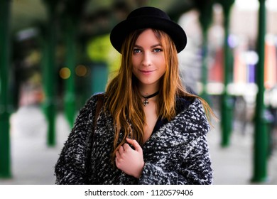 Young pretty girl in a hat. girl is holding her coat adjusting it.