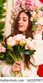Young pretty girl holding flowers in their hands. Portrait of young woman in lilac wreath.