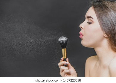 Young pretty girl holds a brush for makeup in her hands. Stand sideways and at the same time it blows the powder for makeup from the brush. Makeup application in close-up.