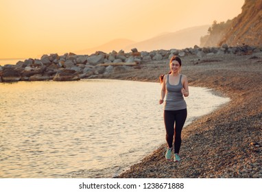 Young pretty girl joging on the beach. Healthy lifestyle. Sunset on the beach at the background.