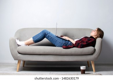 young pretty girl with a laptop lying on the couch and relax, a woman using a computer against a white blank wall, she freelancing and printing text, copy space