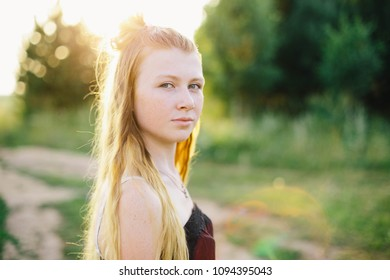 Young pretty girl looks at the camera on the background of the forest at sunset