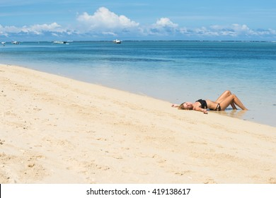Young and pretty girl model in a bikini sunbathing on the beach resort of the Indian Ocean. Mauritius island