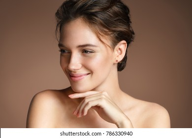 Young pretty girl with naturarl makeup on beige background. Skin care concept