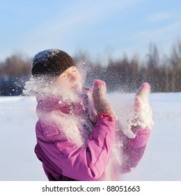 Young pretty girl playing snowball fight