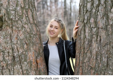 Young pretty girl portrait among big trees outdoor