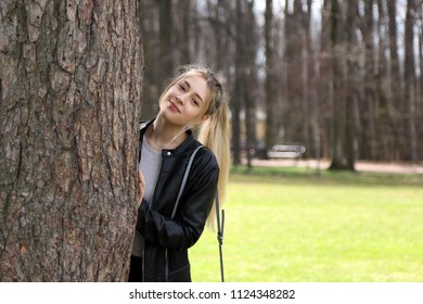 Young pretty girl portrait near big tree outdoor