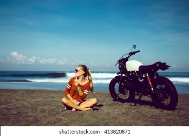 young pretty girl posing on vintage custom motorcycle, outdoor portrait, ocean style hipster, sports wear, denim jeans, sunglasses, freedom, scooter, bike