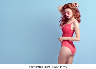 Young Pretty Girl posing in Studio. Beautiful woman in Stylish lace bodysuit, Trendy Curly Hairstyle, Fashion Lingerie. Portrait Sexy playful Redhead Lady on Blue, skin care concept