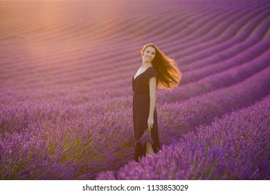 young pretty girl in provence lavender field on the background smiling on the sunset