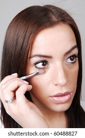 A young pretty girl put the last bit of makeup on her face, over light gray background.