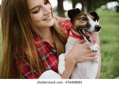 young pretty girl in red tartan shirt and jeans sit at the lawn and hold her dog.