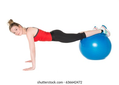Young, pretty girl in red top and black leggings showing how to exercise with the the blue ball on the mat. Full body studio shot, pure white background.