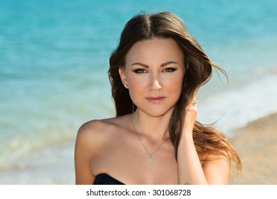 young pretty girl in sexy shorts posing at beach. Fashion summer outdoor portrait of beautiful young woman. Hipster style. slim tanned body,  thin nose