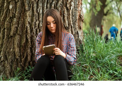 A young, pretty girl in a shirt sits near a tree on the grass on a sunny day with a notebook.