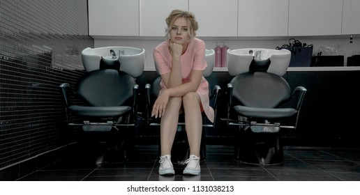 Young pretty girl sit in armchair with washbasin in professional salon