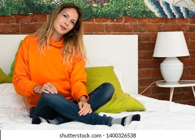 A young pretty girl is sitting on a bed in her room in a bright orange hooded sweatshirt or hoody and blue jeans.