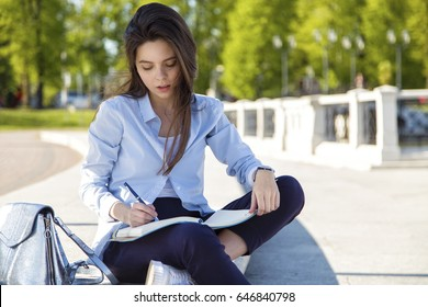 Young pretty girl sitting in park and writing in notebook.