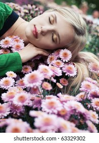 young pretty girl sleeping on flowers outdoors