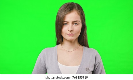 Young pretty girl smiles happily into camera, close up, slow motion over green chroma key screen background