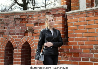 Young pretty girl smiling on red brick wall background outdoor