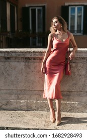 Young pretty girl in stylish fashion dress walk on the street in Rome with bag, sunny day weather. Vacation and female fashion city lifestyle concept