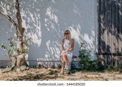 Young pretty girl in sunglasses sits under a tree in the shade at an old white building.