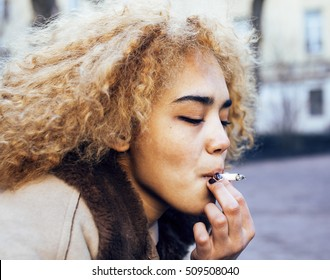 young pretty girl teenage outside smoking cigarette, looking like real junky, social issues conceptyoung pretty girl teenage outside smoking cigarette, looking like real junky, social issues concept