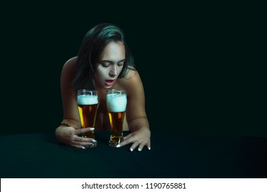 Young pretty girl wants to drink fresh foam beer from two glasses