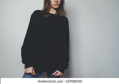 Young pretty girl wearing black template women'?s hoodie with copy space for your design or logo, mock-up of black cotton sweatshirt, white wall in the background with area for your content