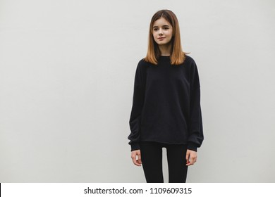 Young pretty girl wearing blank black hoodie with space for your logo or design, mock-up of black cotton sweatshirt, white wall in the background. Front view